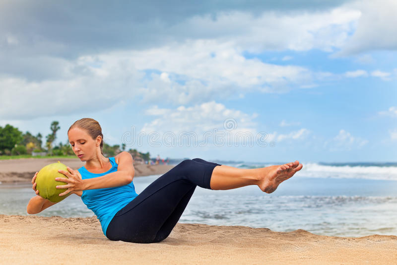 Woman fitness exercise with green coconut on ocean beach stock photography