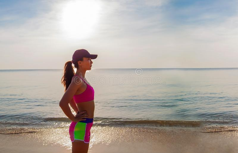 Woman fitness, jogging workout and sport activity on summer holiday.. Active sporty woman run along ocean surf by water pool. Sunset sand beach background with royalty free stock photo