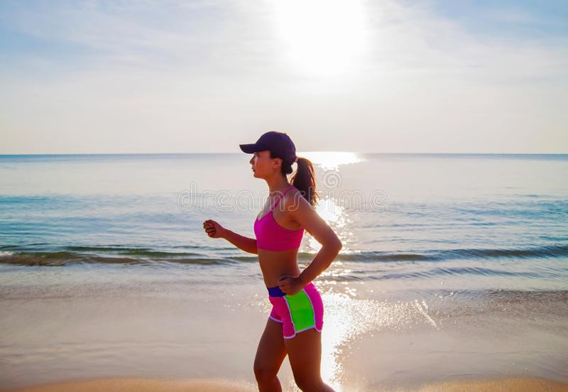 Woman fitness, jogging workout and sport activity on summer holiday.. Active sporty woman run along ocean surf by water pool. Sunset sand beach background with stock images