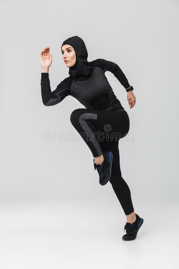 Woman fitness muslim posing running jumping isolated over white wall background stock photos