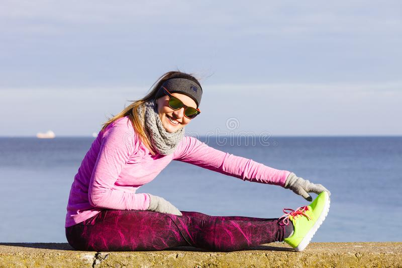 Woman fitness sport girl training outdoor in cold weather. Woman athlete girl training wearing warm sporty clothes outside by seaside in cold weather. Sports and stock photography