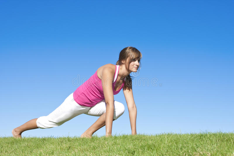 Woman fitness and stretching. A beautiful young woman stretches before fitness and yoga royalty free stock image