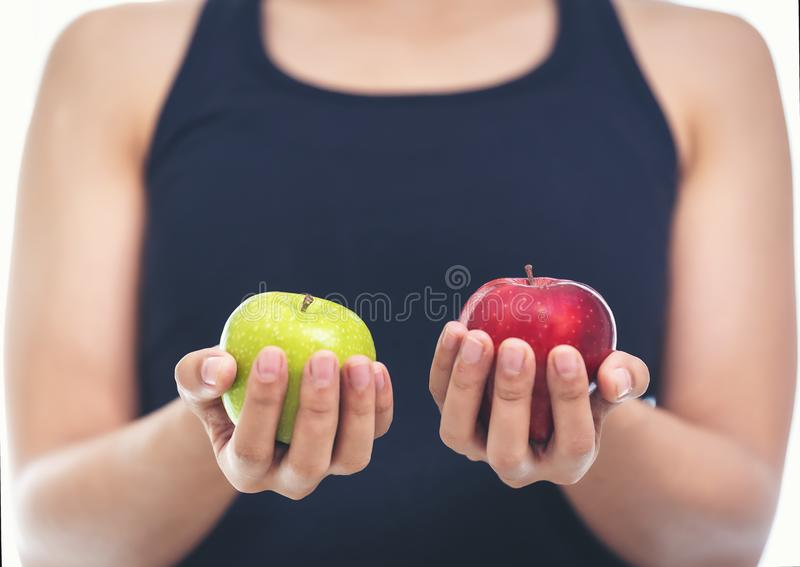 A woman in a fitness suit is holding an apple green and red.Healthy Eating Concept.Focus on apple. royalty free stock photos