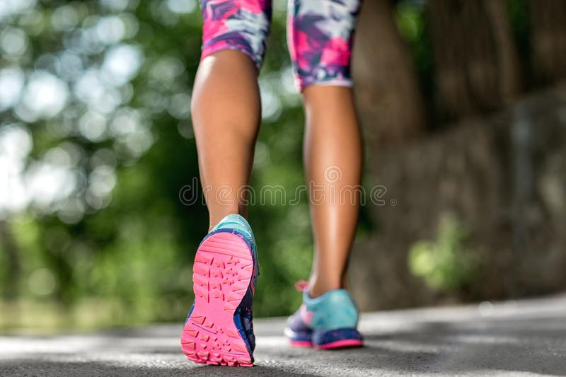 Woman fitness sunrise jog workout welness concept. Runner feet running on road closeup on shoe. royalty free stock photography