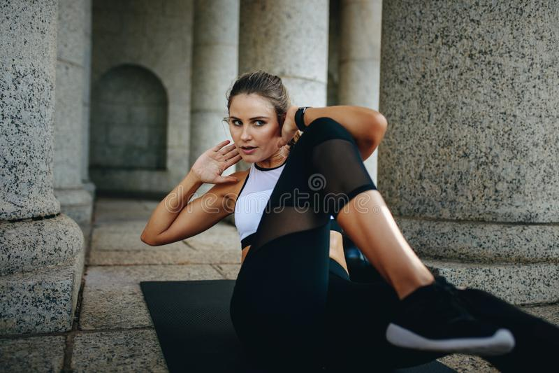 Woman in fitness wear doing abdomen crunches with hands behind her head. Fitness woman training lying on a yoga mat stock photos