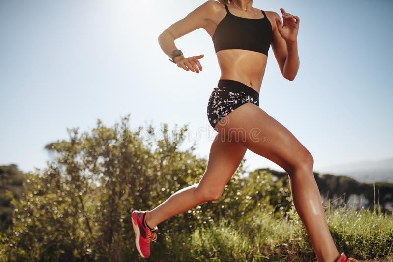 Woman in fitness wear running outdoors with sun flare in the background. Low angle cropped shot of a female runner sprinting.  stock photo