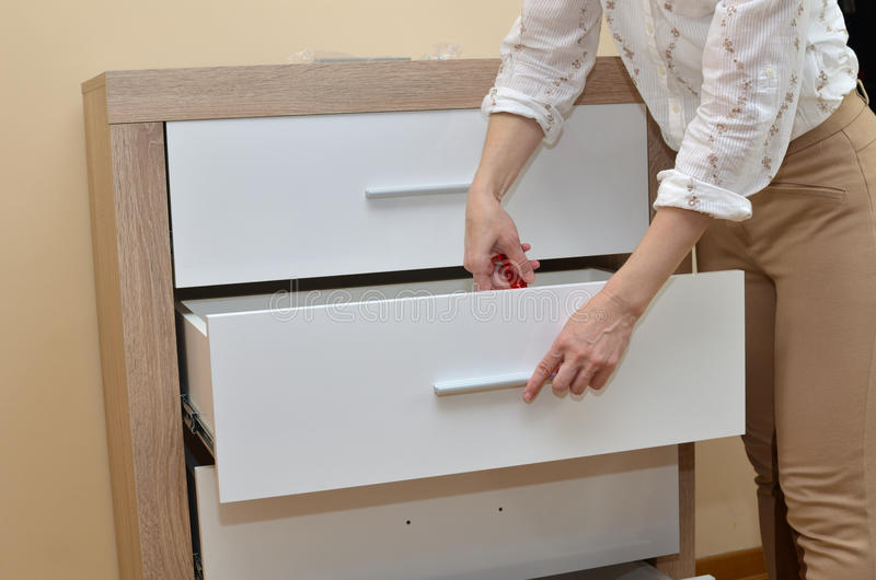 Woman Fixing a Drawer stock images