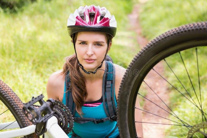Woman fixing her bike royalty free stock photos