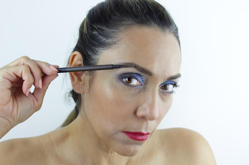 Woman fixing her eye brows stock photography