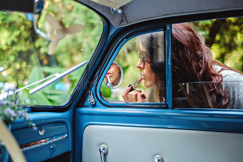Woman fixing lipstick on a classic car mirror. Beautiful sunny day stock photos
