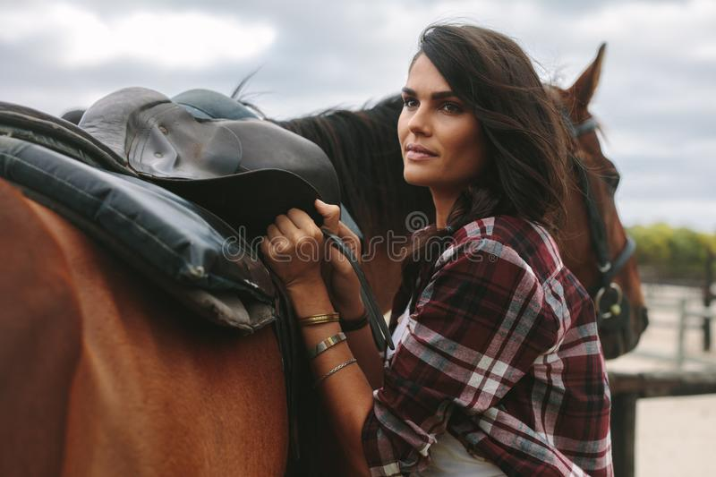 Woman fixing a saddle on her horse royalty free stock photo