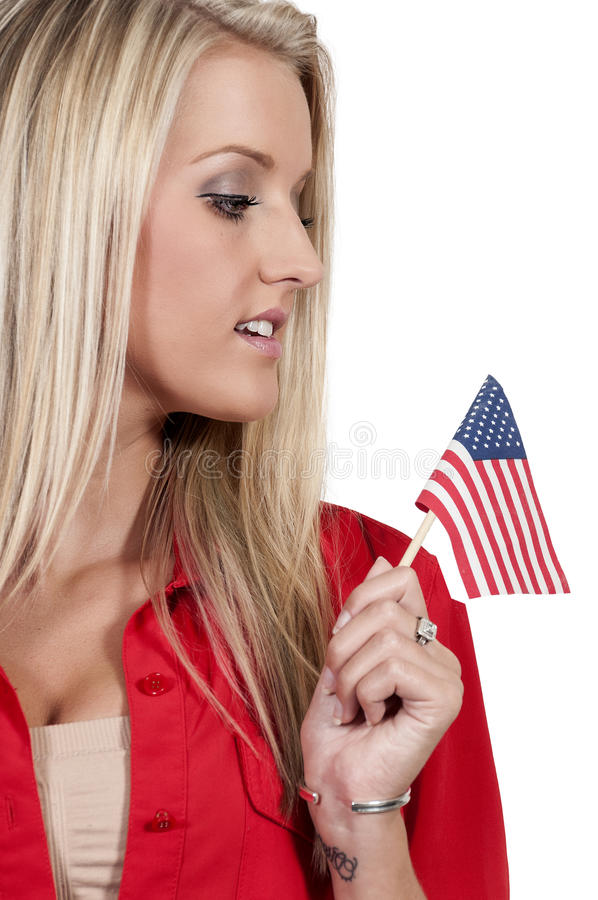 Woman with a Flag. Beautiful young woman holding an American flag royalty free stock photography