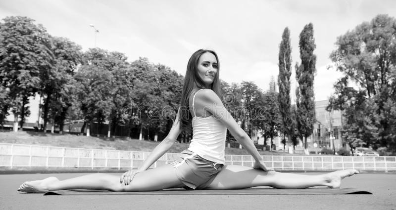 Woman flexible body practice split on fitness mat outdoors nature background. Girl stretching legs after workout. Split. Is easy for her. Stretching muscles stock images