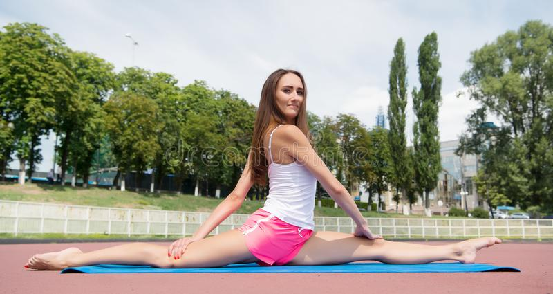 Woman flexible body practice split on fitness mat outdoors nature background. Girl stretching legs after workout. Split. Is easy for her. Stretching muscles stock photography