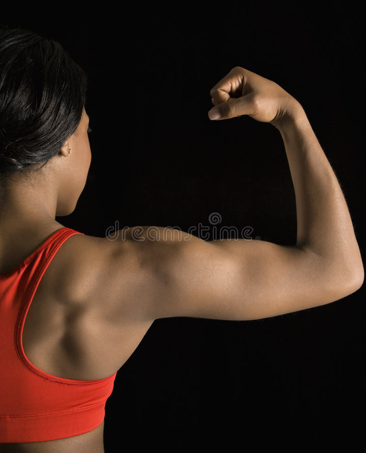 Woman flexing bicep. stock image