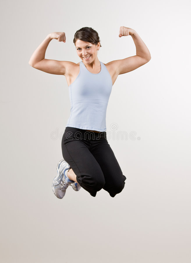 Download Woman Flexing Biceps While Jumping In Mid-air Stock Photo - Image: 6601194