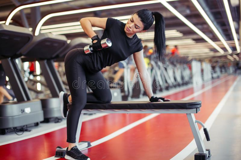 Woman flexing muscles with dumbbell on bench in gym stock image