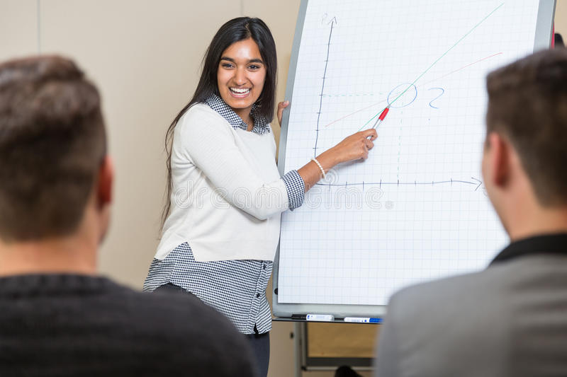 Woman at flip chart giving a lecture and presenting a graph. Woman at flip chart giving a lecture and presenting graph stock photography