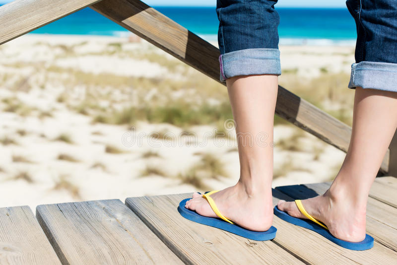 Woman with flip-flops looking at the ocean royalty free stock photography
