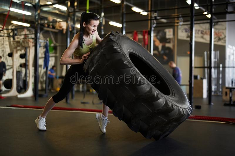 Woman Flipping Truck Tire in Gym stock photo