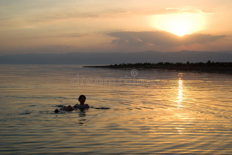 Woman floating in the Dead Sea at sunset. Woman floats in the Dead Sea at sunset, Jordan royalty free stock images