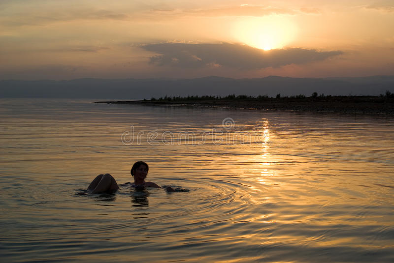 Woman floating in the Dead Sea at sunset. Woman floats in the Dead Sea at sunset, Jordan royalty free stock image