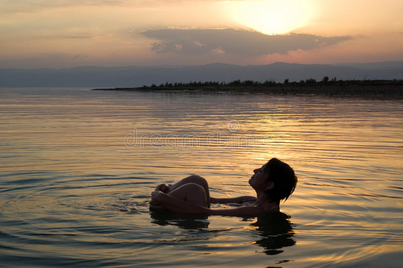 Woman floating in the Dead Sea at sunset stock photography