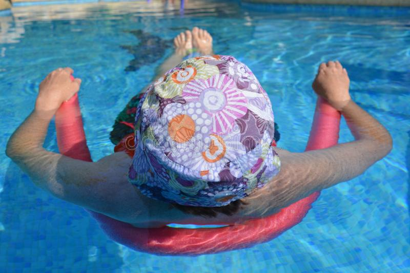 Woman with hat relaxing in a swimming pool, keeping cool stock photography