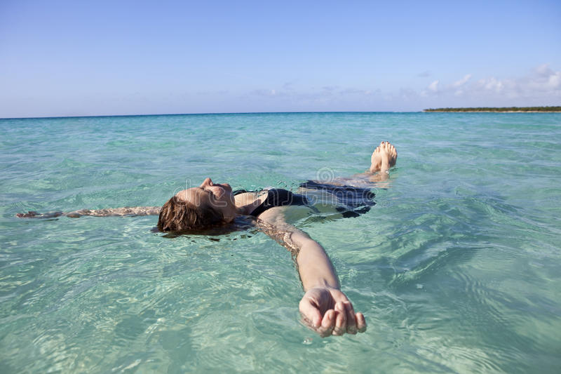 Woman floating in the sea stock image