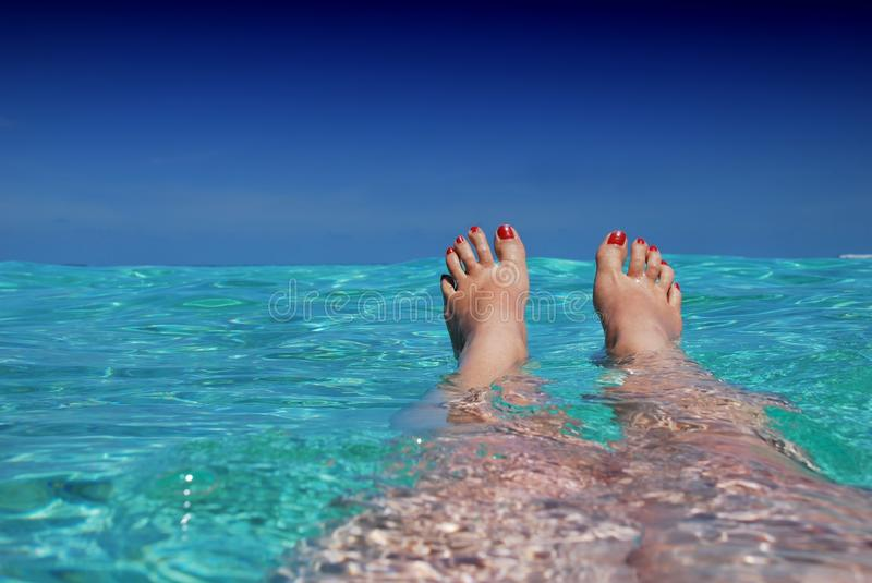 Woman floating in sea stock photos