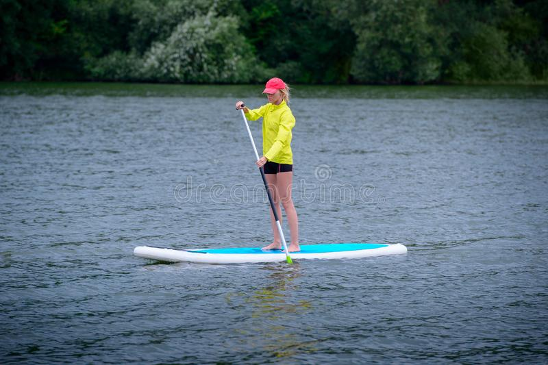 A woman is floating on a SUP board along a large river. Stand on the paddle boarding - amazing outdoor activities. The woman is floating on a SUP board along a stock images