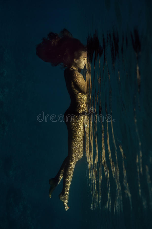 Woman floating underwater royalty free stock image