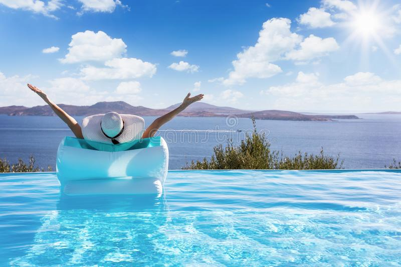 Woman floats on a pool with view to the Mediterranean sea stock photo