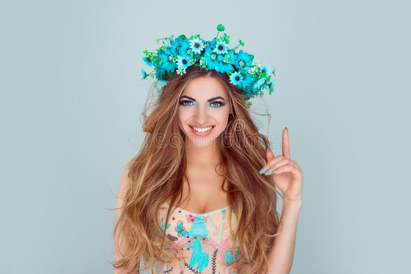 Woman with floral crown on head pointing index finger up laughing royalty free stock photos