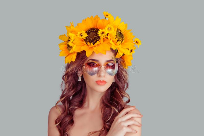 Woman in floral crown from sunflowers, posing with sunglasses in heartshape royalty free stock photos