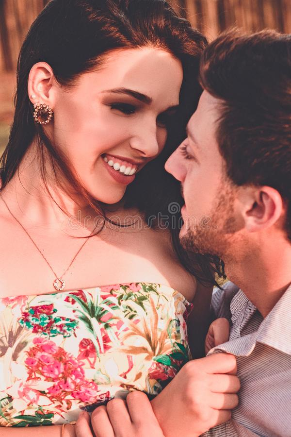 Woman In Floral Dress Looking At Man In Grey Collared Top stock photo
