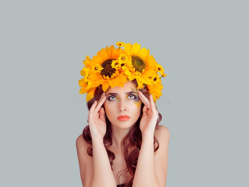 Woman with floral headband hands on temples head thinking deeply royalty free stock photo