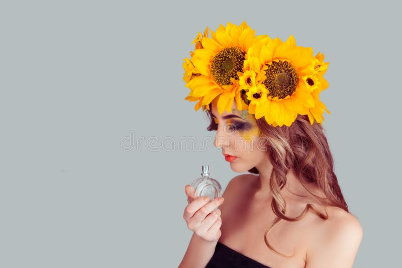 Woman with floral headband holding perfume bottle smelling aroma royalty free stock photos