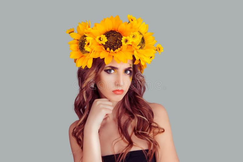 Woman with floral headband looking at you camera pensive hand on chin stock photography