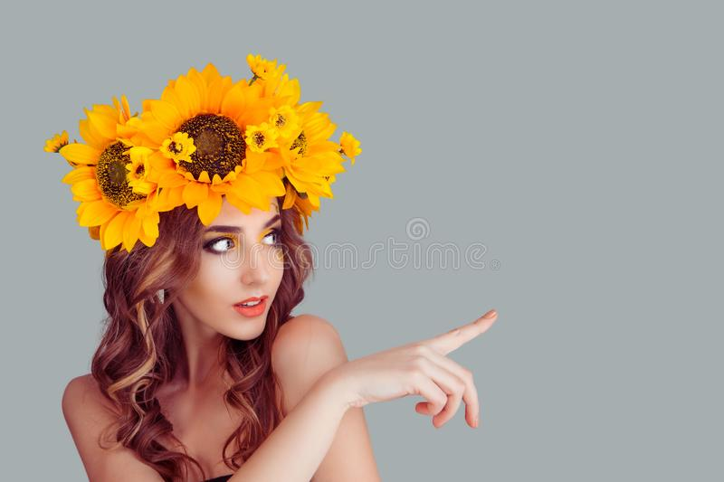 Woman with floral headband pointing away up aside stock photo