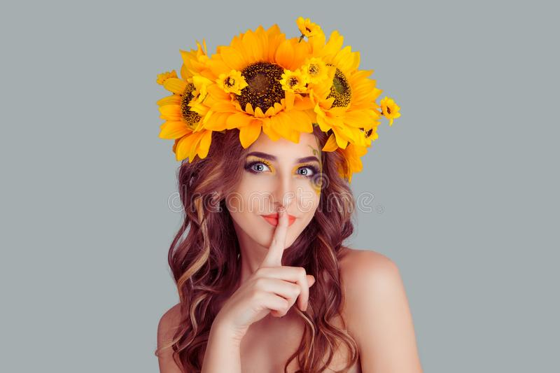 Woman floral headband smiling with hush sign gesture royalty free stock photo
