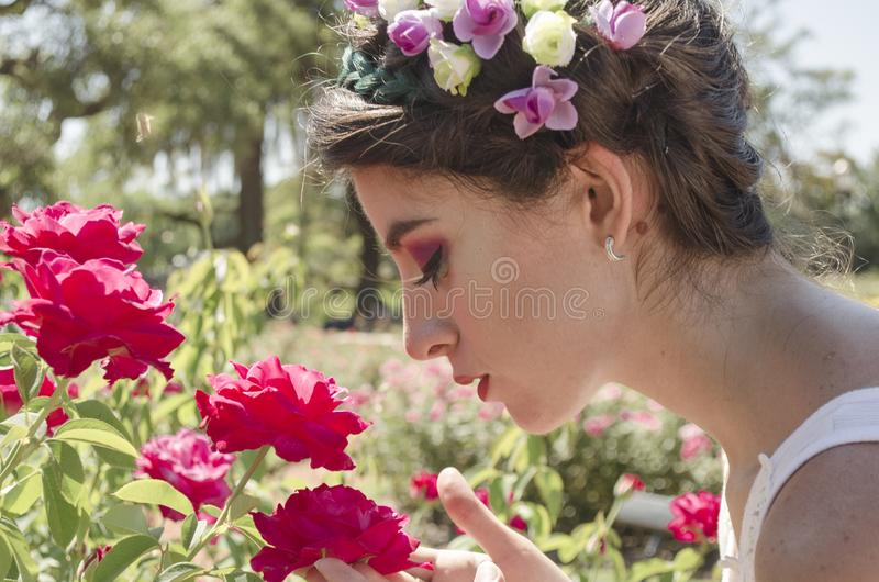 Woman in Floral Headdress Sniffing on Red Flowers royalty free stock photography