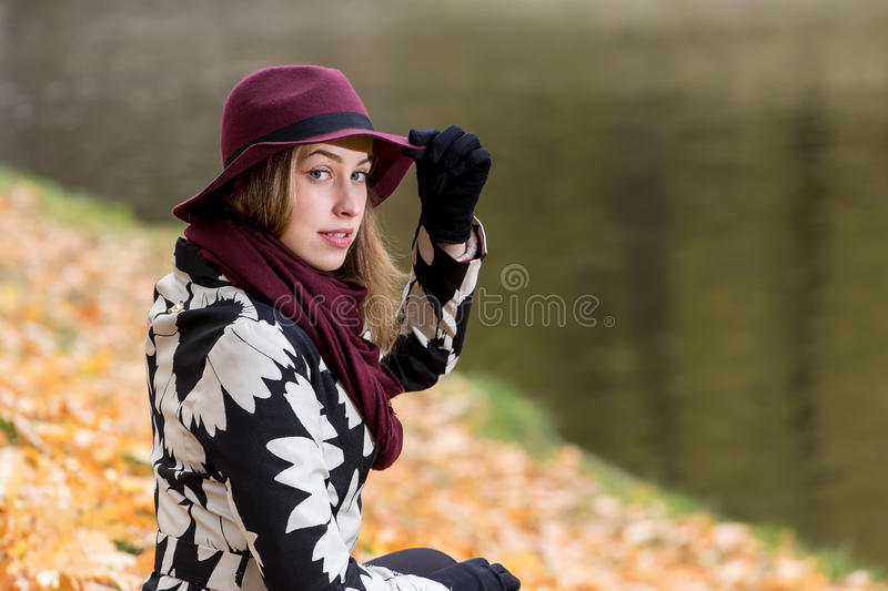 Woman in a floral patterned coat and wine red hat in the park, by the river. Happy girl, colorful autumn forest. Portrait of lady royalty free stock images