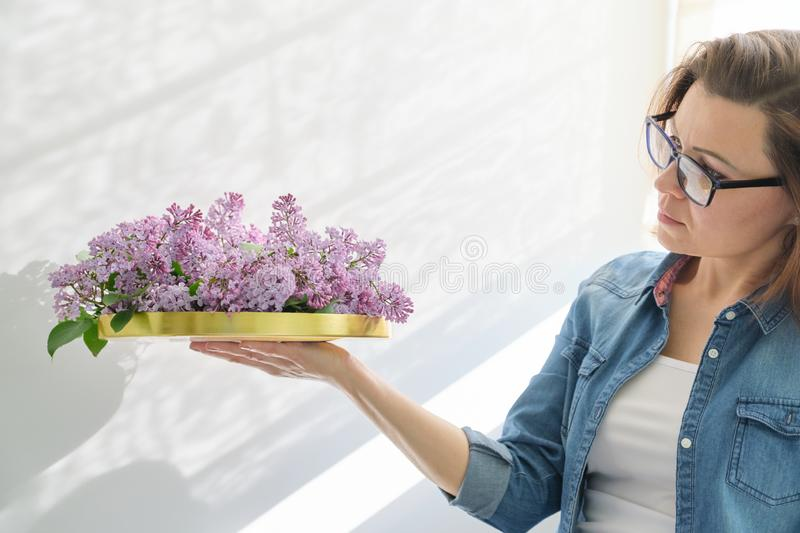 Female holding golden tray with flowers in her hands for interior decoration royalty free stock photography