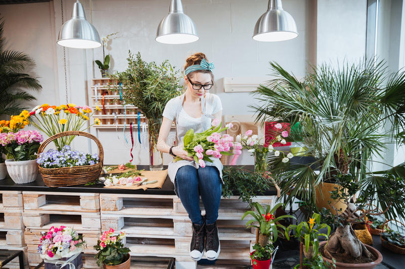 Woman florist sitting and arranging pink tulips in flower shop stock image
