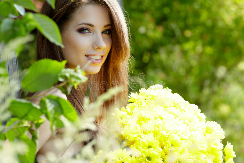 Woman with flower bouquet. Happy smiling young woman with flower bouquet over yellow green rapeseed meadow royalty free stock photography