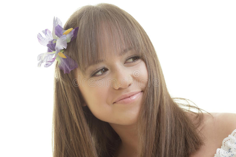 Woman with a flower in her hair. Beautiful young woman posing with a flower in her hair royalty free stock image