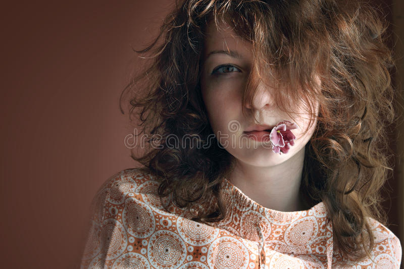 Woman with a flower in a mouth royalty free stock image