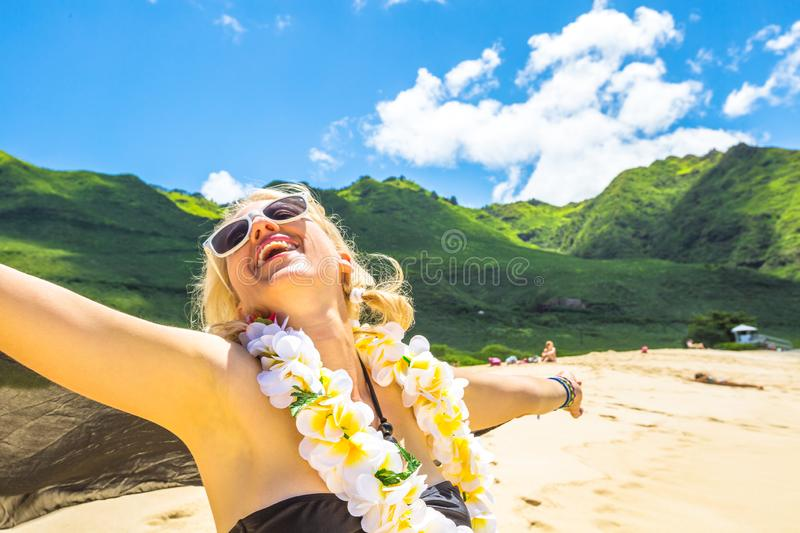 Woman with flower neck garland. In bikini woman on Makua Beach, Waianae coast, Hawaii. On background: Waianae Mountains and Makua Valley, Oahu island. Travel stock image