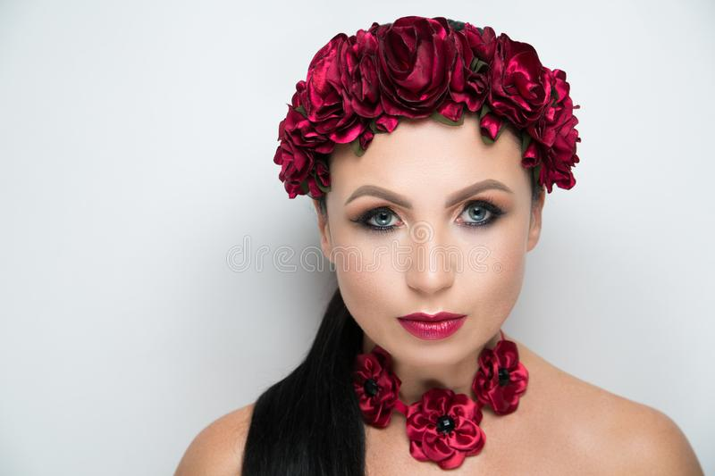 Woman flower wreath. Young beautiful girl lady model with a fashionable flower tiara. professional make-up arrows eye shadows long lashes, stylish matte vine stock photos